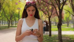 Woman reading message in smartphone walking at summer park stock video