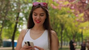 Woman reading message in smartphone walking at summer park stock footage