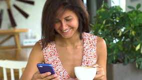 Woman reading message on smartphone, drinking coffee and laugh stock footage