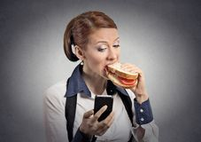 Woman reading message on smartphone eating sandwich. Closeup portrait young serious corporate business woman deal maker reading news message on smart mobile stock photos