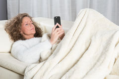 Woman reading message on smartphone Stock Images