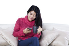Woman reading messages on a smartphone on studio Stock Photo