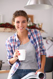 Woman reading mgazine In kitchen at home Royalty Free Stock Photo