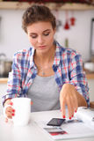 Woman reading mgazine In kitchen at home Royalty Free Stock Image