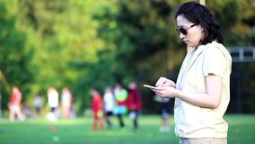 Woman reading mobile phone message. At sport field stock video
