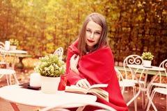 Woman Reading modèle un livre dans un café dehors photo libre de droits