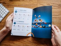 Woman reading about Nespresso advertising catalogue stock photos