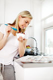 Woman reading the news at breakfast. Attractive young blonde woman standing reading the newspaper at the kitchen counter while enjoying her breakfast Stock Images