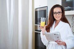 Woman reading the news while drinking orange juice Royalty Free Stock Photo