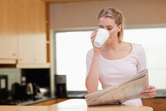 Woman reading the news while having coffee Royalty Free Stock Image