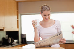 Woman reading the news while having tea Stock Image