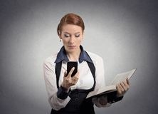 Woman reading news on smart phone holding book Royalty Free Stock Image