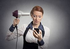 Woman reading news on smartphone holding hairdryer. Closeup portrait business woman deal maker reading news on smartphone looking at mobile phone holding Royalty Free Stock Image