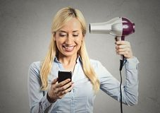 Woman reading news on smartphone holding hairdryer Royalty Free Stock Images