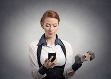 Woman reading news on smartphone lifting dumbbell Stock Photography