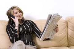 Woman reading newspaper. Beautiful woman sitting on the sofa in living room wearing businesss wear and reading newspaper Royalty Free Stock Images