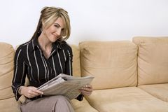 Woman reading newspaper. Beautiful woman sitting on the sofa in living room wearing businesss wear and reading newspaper Royalty Free Stock Image