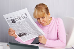 Woman reading newspaper - bad news Stock Photography