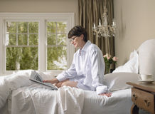 Woman Reading Newspaper In Bed Royalty Free Stock Photos