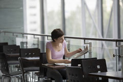 Woman Reading Newspaper At Cafe royalty free stock photography