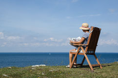 Woman reading newspaper in a chair with beautiful view Stock Image