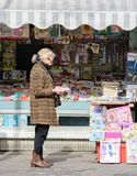 An elderly woman is reading a newspaper outside a newspaper store. On the counter are magazines and newspapers. Woman reading a newspaper. Florence. Italy. 18 royalty free stock photography