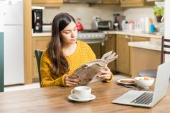 Woman Reading Newspaper While Having Morning Meal. Attractive woman reading daily news while having breakfast at home stock photos