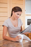 Woman reading newspaper while holding cup of coffee Royalty Free Stock Photo