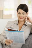 Woman reading newspaper at home Royalty Free Stock Images