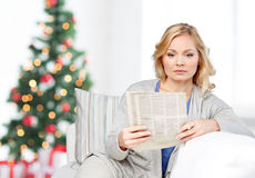 Woman reading newspaper at home Stock Images