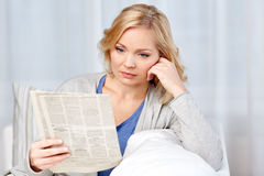 Woman reading newspaper at home Stock Photo