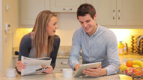 Woman reading newspaper with man holding a tablet PC. Woman reading the newspaper with man holding a tablet PC in the kitchen stock footage