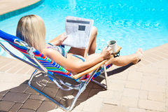 The woman reading newspaper near the pool Royalty Free Stock Images