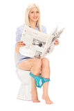 Woman reading a newspaper seated on toilet Royalty Free Stock Photo