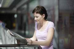 Woman Reading Newspaper In Shopping Centre Royalty Free Stock Images