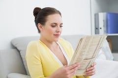 Woman reading newspaper on sofa Stock Image