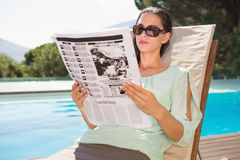 Woman reading newspaper on sun lounger by pool Royalty Free Stock Photo