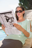 Woman reading newspaper on sun lounger by pool Stock Photo