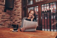 Woman reading a newspaper and talking on mobile phone stock photos