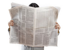 Woman reading newspaper on white background stock images