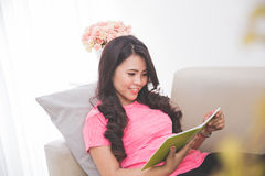 Woman reading notebook sitting on a couch Royalty Free Stock Image