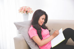 Woman reading notebook sitting on a couch Royalty Free Stock Images