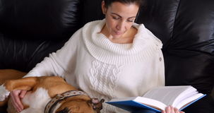 Woman reading a novel while dog relaxing on her lap. In living room stock video footage