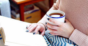 Woman reading a novel while having coffee in living room. At home stock footage