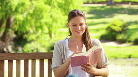 Woman reading a novel in a park. While sitting on a bench stock footage