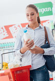 Woman reading nutrition facts. Woman shopping at the supermarket and reading a food label on a milk bottle Royalty Free Stock Photos
