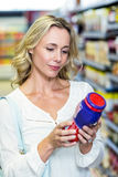Woman reading nutritional values. At supermarket Stock Images