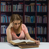 Woman reading an open old book in front of a book shelf Stock Images