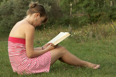 Woman reading outdoors. Woman reading book in the park outdoors Royalty Free Stock Images