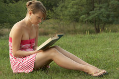 Woman reading outdoors. Woman reading book in the park outdoors Royalty Free Stock Photo